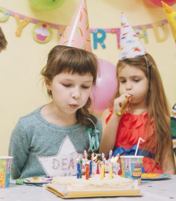kids-blowing-candles-cake_23-2147773150